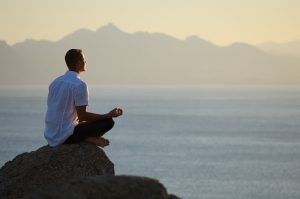 Guy sitting on a rock in the lotus position, meditating.