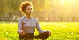 African American Woman Meditating In Nature.