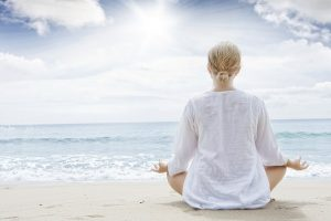 Image of the back of a lovely blond woman meditating at the beach with the sparkling ocean.
