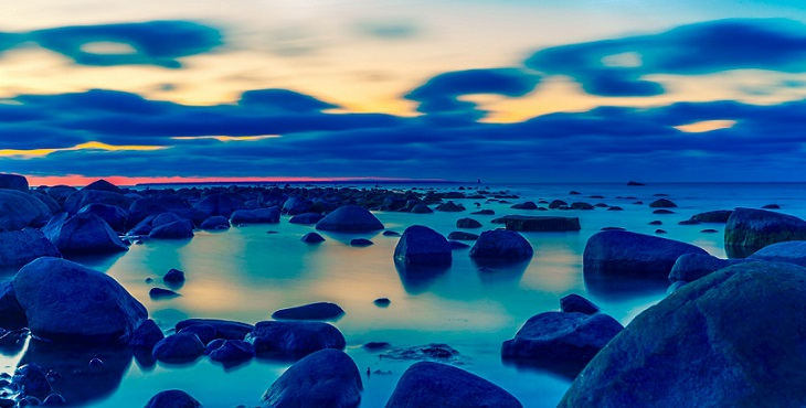 Image of a blue sunset along the rocks and lake. The Act Of Blessing And Living A Blessed Life